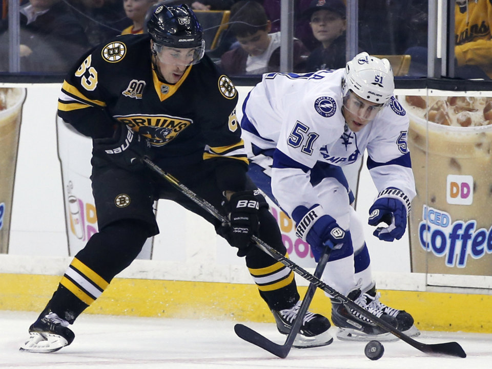 Photo - Boston Bruins left wing Brad Marchand (63) and Tampa Bay Lightning center Valtteri Filppula (51) compete for control of the puck during the first period of an NHL hockey game in Boston Monday, Nov. 11, 2013. (AP Photo/Elise Amendola)