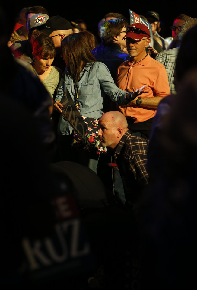 Photo - A man kneels over a supporter who collapsed near the stage before Republican presidential candidate Ted Cruz spoke in the Chevy Bricktown Event Center at a rally on Sunday, Feb. 28, 2016 in Oklahoma City, Okla.  Photo by Steve Sisney, The Oklahoman
