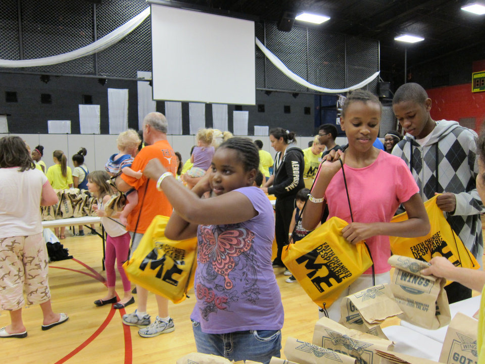 "Photo -  Roni and Nia Alexander grab bags filled with lunch provided by volunteers at OKC Faith Church during the ministry's 2013 ""Feeding the 5000"" school supply giveaway at the church, 800 S Portland. Photo by Carla Hinton, The Oklahoman Archives    CARLA HINTON -"