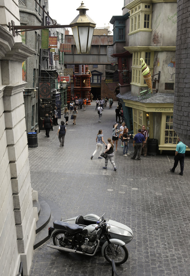 Photo - People walk along Diagon Alley during a preview at the Wizarding World of Harry Potter at Universal Orlando, Thursday, June 19, 2014, in Orlando, Fla. (AP Photo/John Raoux)