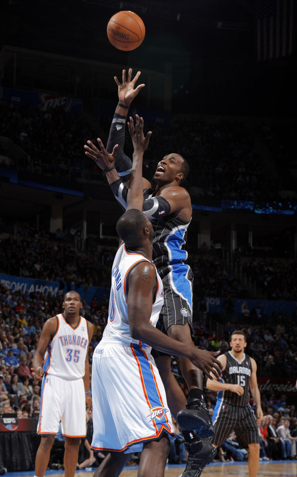 Orlando Magic's Dwight Howard (12) shoots over Oklahoma City Thunder's Nazr Mohammed (8) during the opening day NBA basketball game between the Oklahoma CIty Thunder and the Orlando Magic at Chesapeake Energy Arena in Oklahoma City, Sunday, Dec. 25, 2011. Photo by Sarah Phipps, The Oklahoman