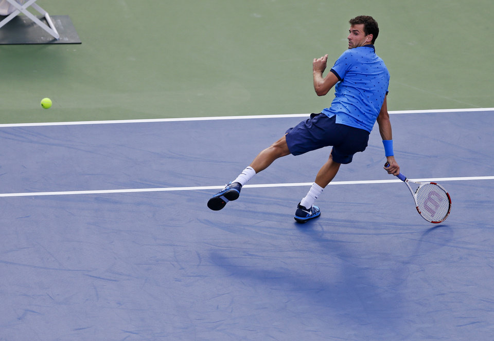 Photo - Grigor Dimitrov, of Bulgaria, returns a shot against Gael Monfils, of France, during the fourth round of the 2014 U.S. Open tennis tournament, Tuesday, Sept. 2, 2014, in New York. (AP Photo/Darron Cummings)