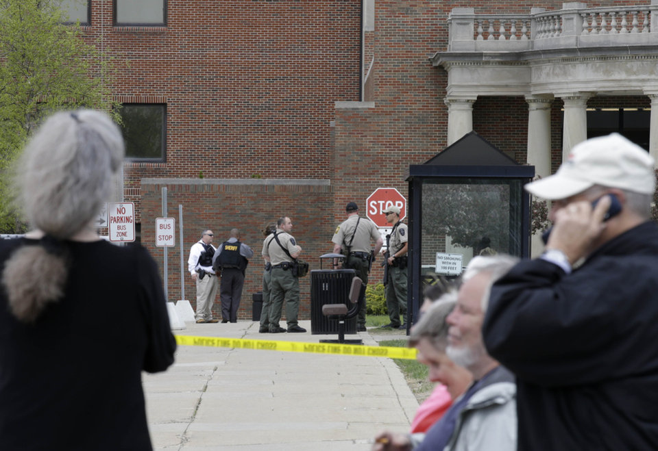 Photo - People watch police officials as they wait outside a Veterans Affairs hospital after they were evacuated, Monday, May 5, 2014, in Dayton, Ohio. A city official says a suspect is in police custody after a shooting at the Veterans Affairs hospital that left one person with a minor injury. (AP Photo/Al Behrman)