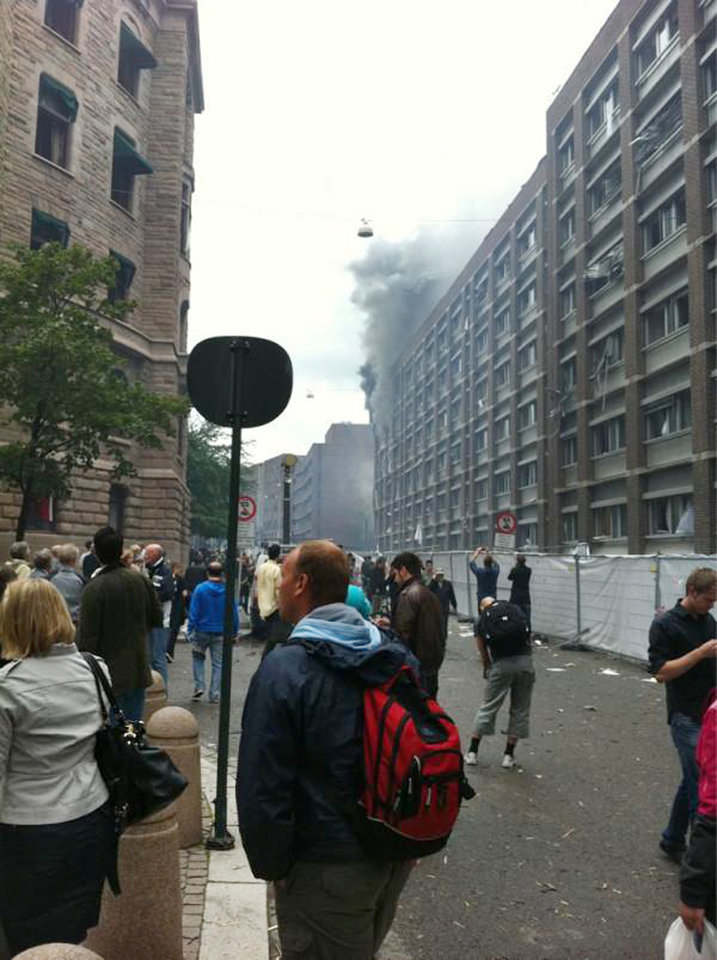 Photo - Pedestrians watch the smoke rise from government buildings in the center of Oslo, Norway, Friday, July 22, 2011, following an explosion that tore open several buildings including the prime minister's office, shattering windows and covering the street with documents. (AP Photo/Gregers Rygg
