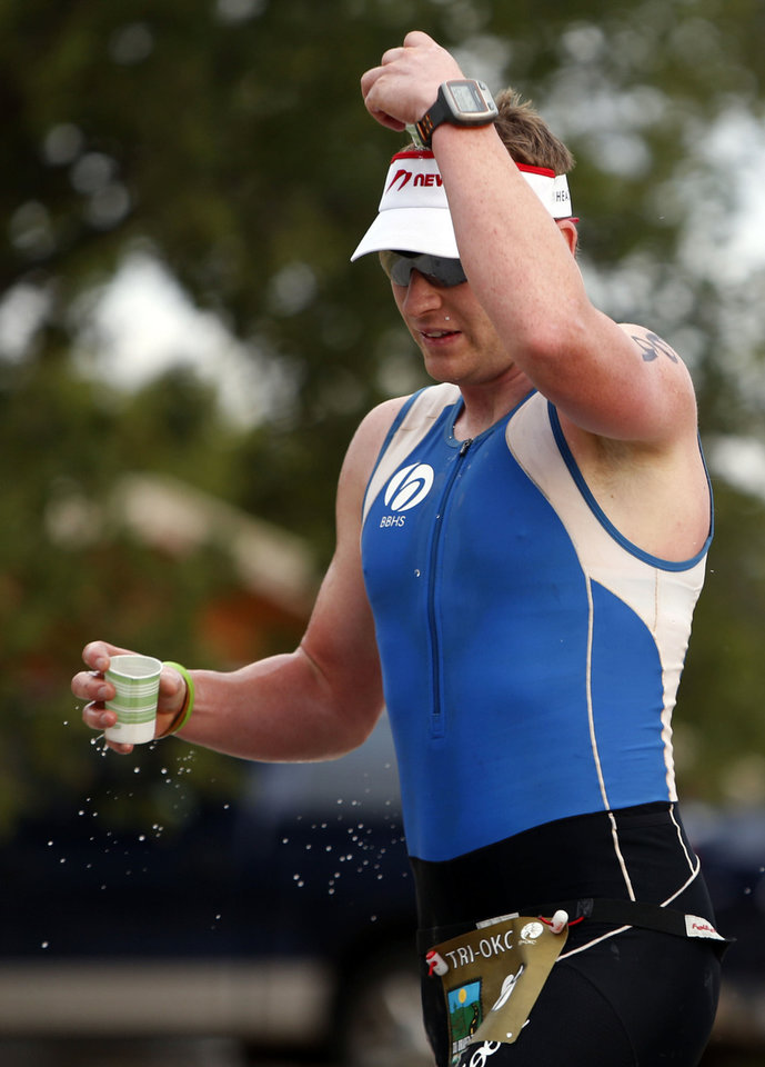 Photo - Right: Michael Zelten pours water on his head during the triathlon.