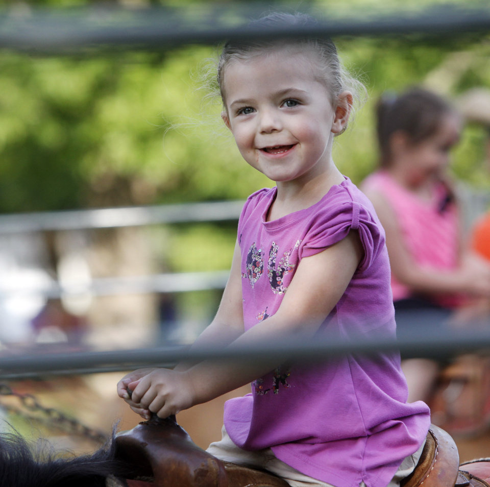 Photo -  Emerson Terska, 3, of Edmond, rides a pony during a picnic celebrating the 125th anniversary of the founding of the St. John the Baptist Catholic Church in Edmond. Photo by K.T. King, The Oklahoman   KT King -