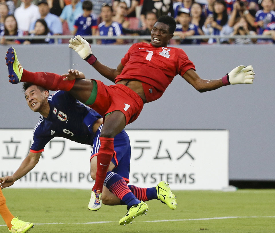 Photo - Japan's Shinji Okazaki (9) and Zambia goal keeper Toaster Nsabata (1) fall to the ground after a collision while going up for the ball during the first half of an international friendly soccer match in Tampa, Fla., Friday, June 6, 2014. Both players were injured but remained in the game.(AP Photo/John Raoux)