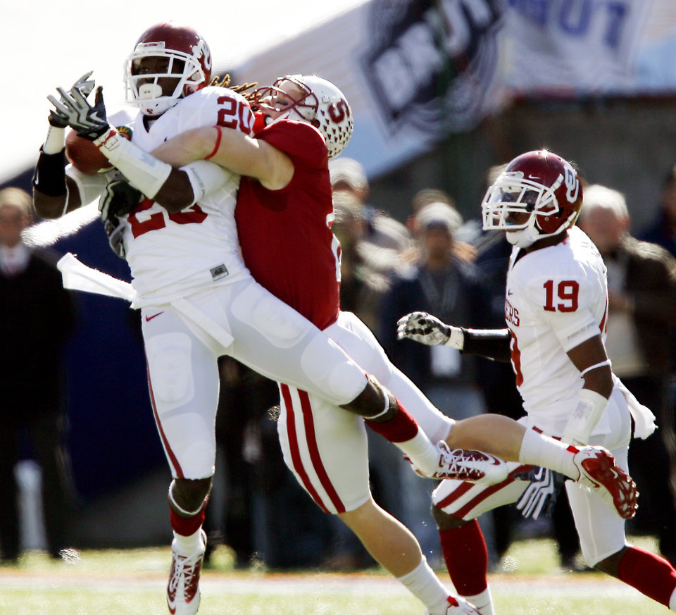 Photo - Oklahoma's Quinton Carter (20) intercepts a pass in front of Stanford's Ryan Whalen (8) during the first half of the Brut Sun Bowl college football game between the University of Oklahoma Sooners (OU) and the Stanford University Cardinal on Thursday, Dec. 31, 2009, in El Paso, Tex.   Photo by Chris Landsberger, The Oklahoman