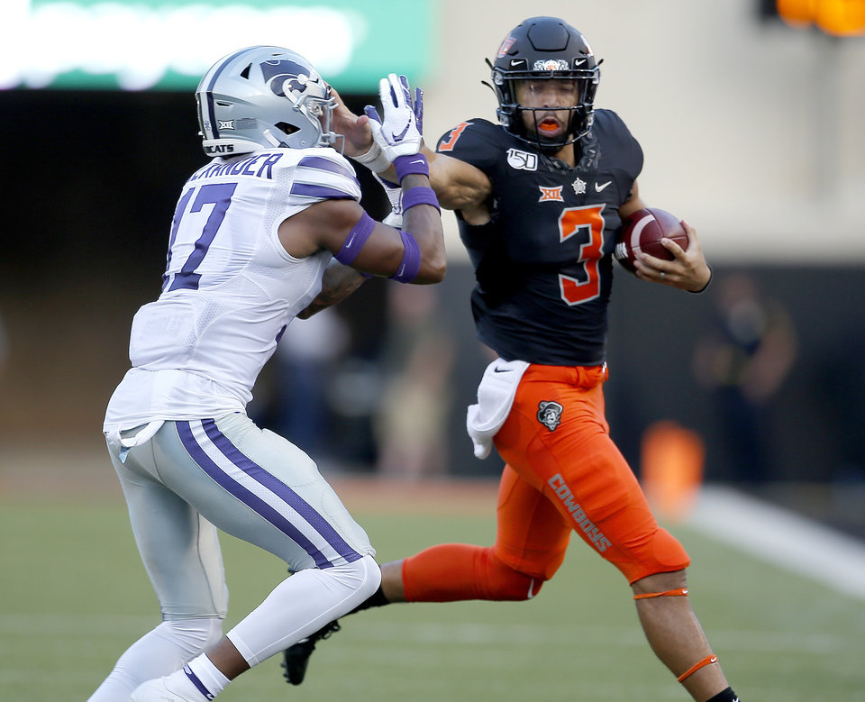 Photo - Oklahoma State's Spencer Sanders (3) tries to get by Kansas State's Jonathan Alexander (17) in the first quarter during the college football game between the Oklahoma State Cowboys and the Kansas State Wildcats at Boone Pickens Stadium in Stillwater, Okla., Friday, Sept. 27, 2019. [Sarah Phipps/The Oklahoman]