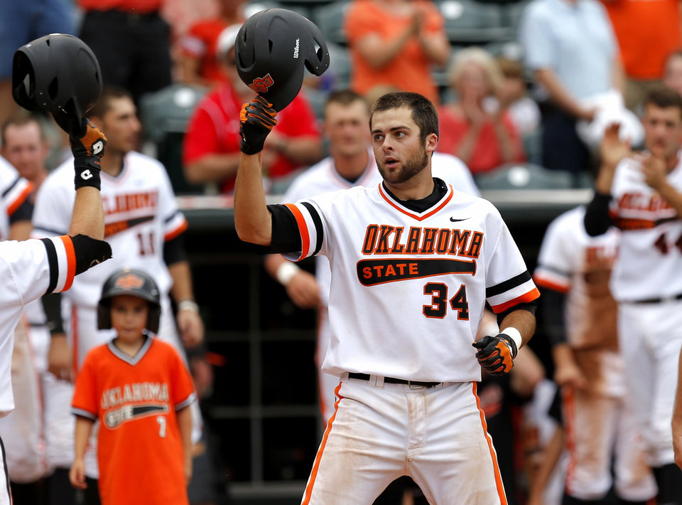 Photo - OSU's Bryan Case celebrates after scoring on a home run on the third inning of a Big 12 Tournament baseball game between Oklahoma State University and the University of Texas at Chickasaw Bricktown Ballpark in Oklahoma City, Saturday, May 24, 2014. Photo by Bryan Terry The Oklahoman