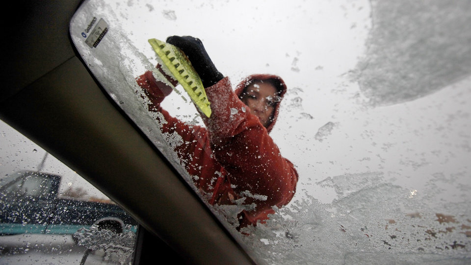 Photo - Tara Nunley of Oklahoma City clears off her windshield in Oklahoma City, Thursday, Jan. 28, 2010.  Photo by Bryan Terry, The Oklahoman