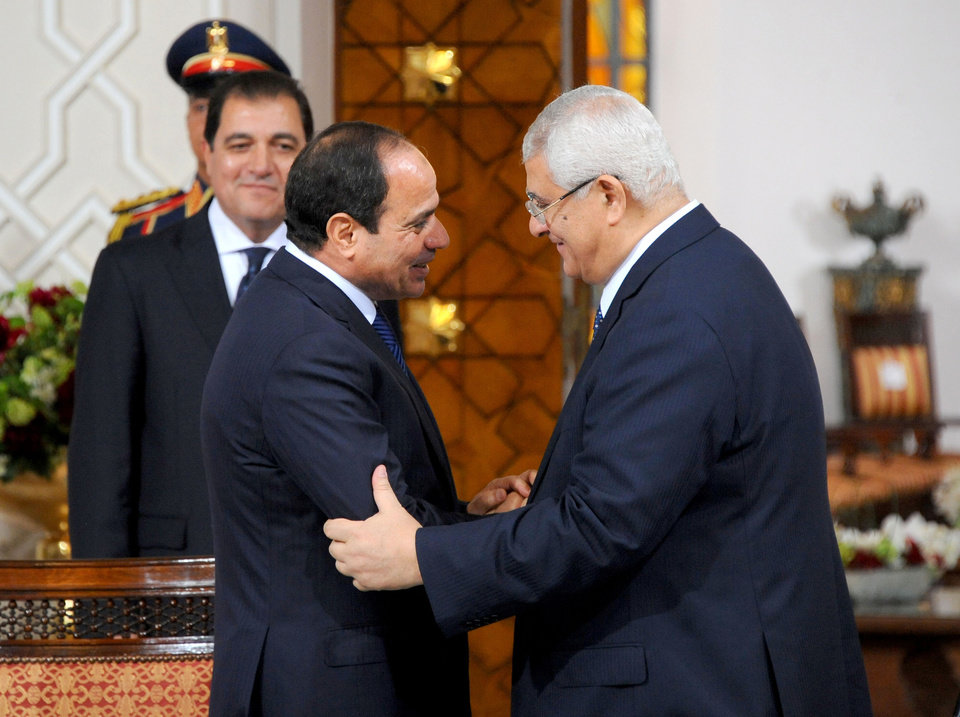 Photo - In this photo provided by Egypt's state news agency MENA, Egyptian President Abdel-Fattah el-Sissi, left, and interim President Adly Mansour shake hands after signing a