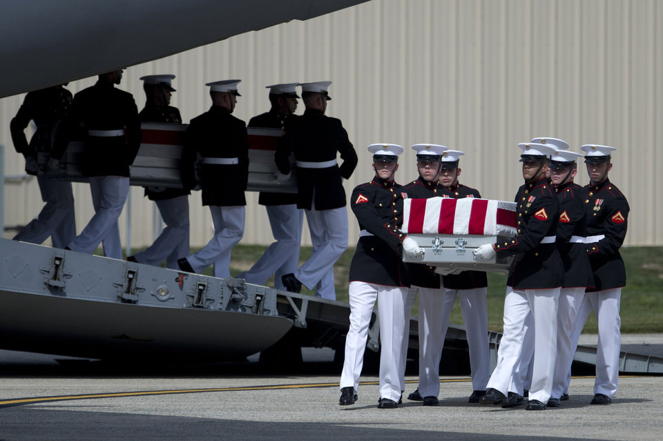 Photo -   Carry teams move flag draped transfer cases of the remains of the four Americans killed this week in Benghazi, Libya, from a transport plane during the Transfer of Remains Ceremony, Friday, Sept. 14, 2012, at Andrews Air Force Base, Md., marking the return to the United States of the remains of the four Americans killed this week in Benghazi, Libya. (AP Photo/Carolyn Kaster)
