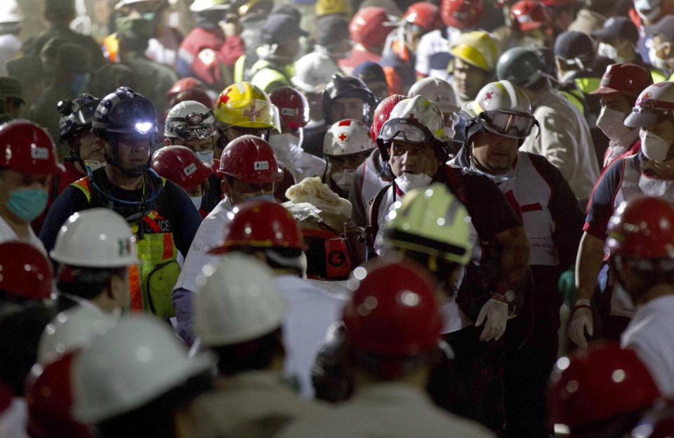 Photo - Rescue workers carry an injured survivor after an explosion in a building at Mexico's state-owned oil company PEMEX complex, in Mexico City, Thursday Jan. 31, 2013. The explosion killed more than 10 people and injured some 80 as it heavily damaged three floors of the building. According to civil protection and local media some people remained trapped in the debris from the explosion, which occurred in the basement of an administrative building next to the iconic, 52-story tower of Petroleos Mexicanos, or PEMEX. (AP Photo/Eduardo Verdugo)