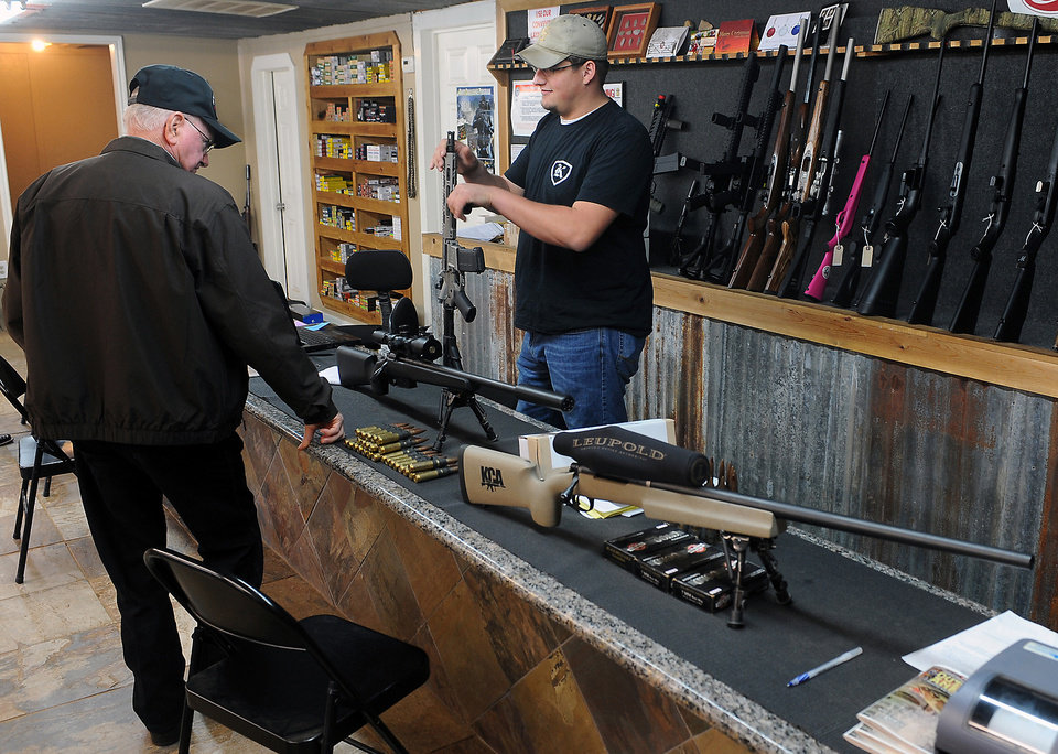 FILE - In this Thursday, Dec. 20, 2012 file photo, Clerk Lance McCoy, right, shows a variety of weapons including an AR-15 style semi-automatic at Kizer Guns and Ammo near Nacogdoches, Texas. Demand for firearms, ammunition and bulletproof gear has jumped since the Dec. 14 school shooting in Newtown, Conn., that killed 20 children and six adults. Politicians, including President Barack Obama, have called for tighter gun control since then. That has sent Americans into a panic, buying as many guns and as much ammunition as they can get their hands on before any type of ban is set. (AP Photo/The Daily Sentinel, Andrew D. Brosig, File) MANDATORY CREDIT