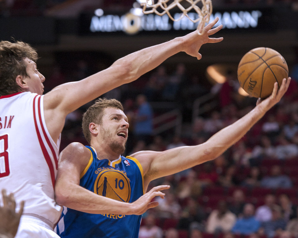 Golden State Warriors' David Lee (10) drives by Houston Rockets' Omer Asik, left, during the first quarter of an NBA basketball game, Tuesday, Feb. 5, 2013, in Houston. (AP Photo/Dave Einsel)