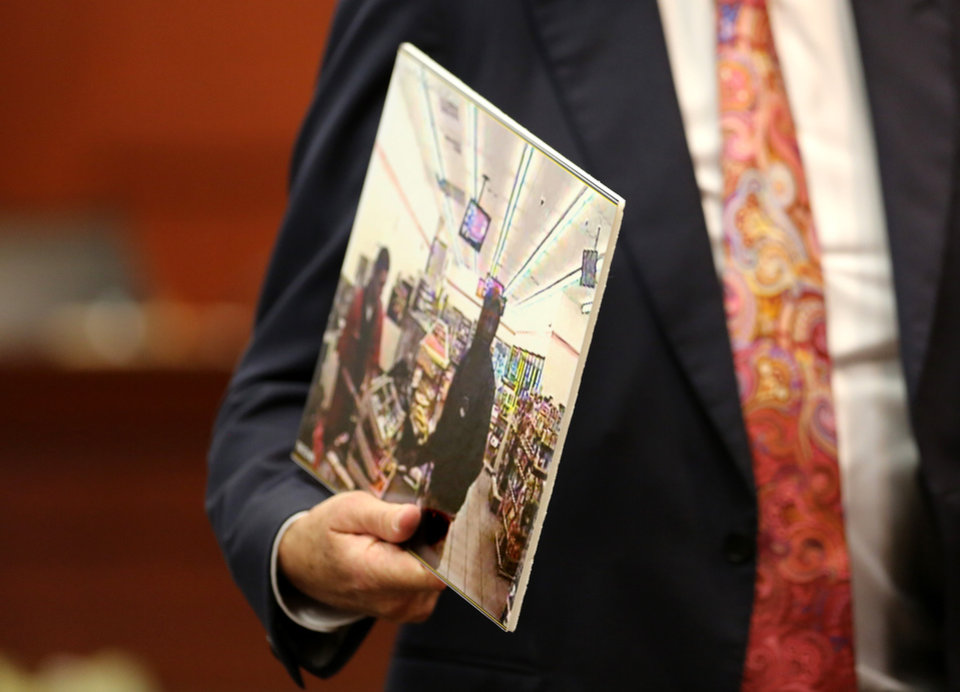 Photo - Attorney Mark O'Mara, defense counsel for George Zimmerman, holds an evidence photo of Trayvon Martin while questioning a state witness, on the 15th day of Zimmerman trial in Seminole circuit court, in Sanford, Fla., Friday, June 28, 2013.  Zimmerman has been charged with second-degree murder for the 2012 shooting death of Trayvon Martin.(AP Photo/Orlando Sentinel, Joe Burbank, Pool)