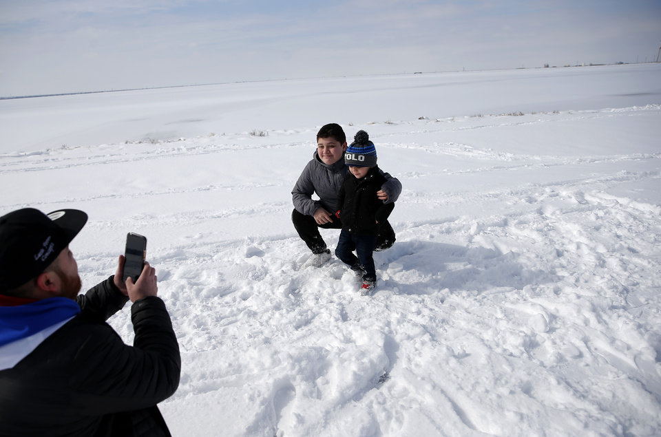 Photo - Ken takes pictures of Adrian and Thiago, right, at Lake Hefner in Oklahoma City, Wednesday, Feb. 17, 2021. [Sarah Phipps/The Oklahoman]