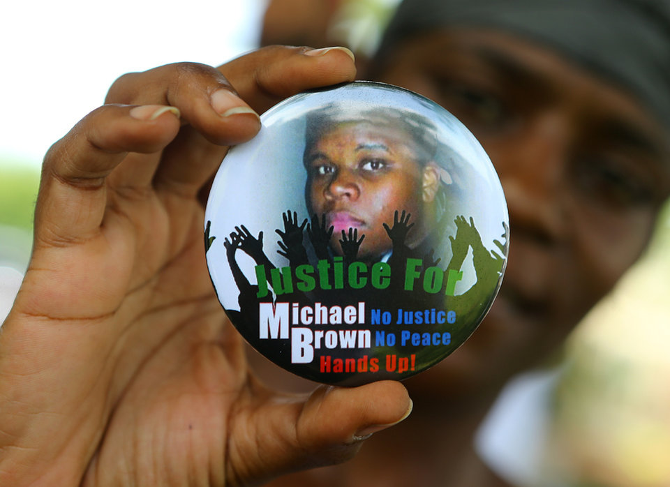 Photo - FILE - In a Thursday, Aug. 21, 2014 file photo, Nikki Jones, of Spanish Lake, Mo, holds a button in support of Michael Brown while visiting the community in the apartment development near where he was fatally shot by police in Ferguson, Mo. Michael Brown Jr. was on the verge of starting college, eager to launch himself into the adult world. Instead, on Monday he'll be mourned at his funeral, more than two weeks after his fatal shooting by a white police officer. (AP Photo/Atlanta Journal Constitution, Curtis Compton, File)