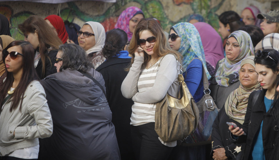 Photo - Egyptian voters line up outside a polling station in Cairo, Egypt, Tuesday, Jan. 14, 2014. Egyptians have started voting on a draft for their country's new constitution that represents a key milestone in a military-backed roadmap put in place after President Mohammed Morsi was overthrown in a popularly backed coup last July. (AP Photo/Amr Nabil)
