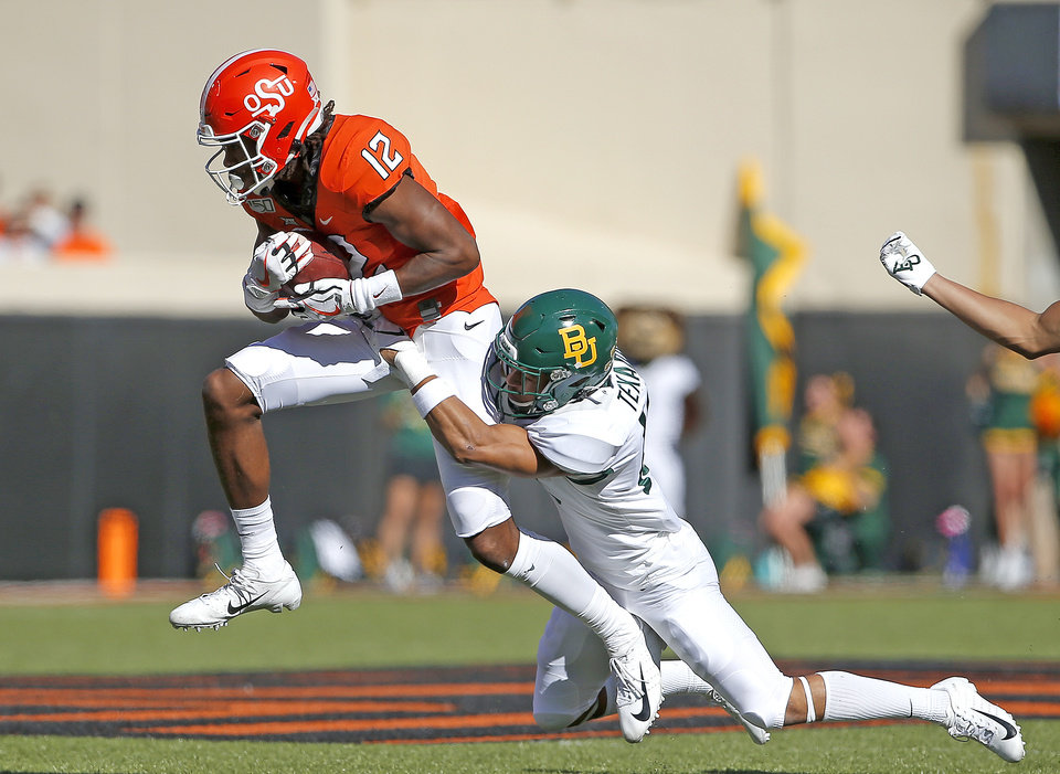 Photo - Oklahoma State's Jordan McCray (12) ties to get by Baylor's Raleigh Texada (13) in the first quarter during the college football game between Oklahoma State University and Baylor at Boone Pickens Stadium in Stillwater, Okla., Saturday, Oct. 19, 2019. [Sarah Phipps/The Oklahoman]