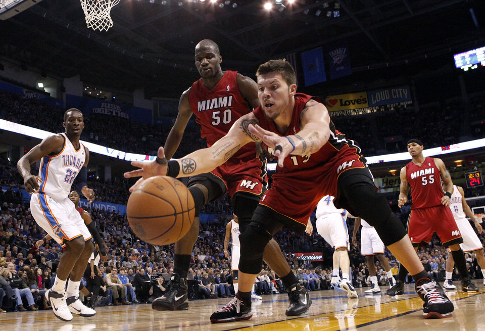 Photo - Miami's Mike Miller (13) grabs a loose ball as Miami's Joel Anthony (50) looks on during the NBA basketball game between Oklahoma City and Miami at the OKC Arena in Oklahoma City, Thursday, Jan. 30, 2011. Photo by Sarah Phipps, The Oklahoman