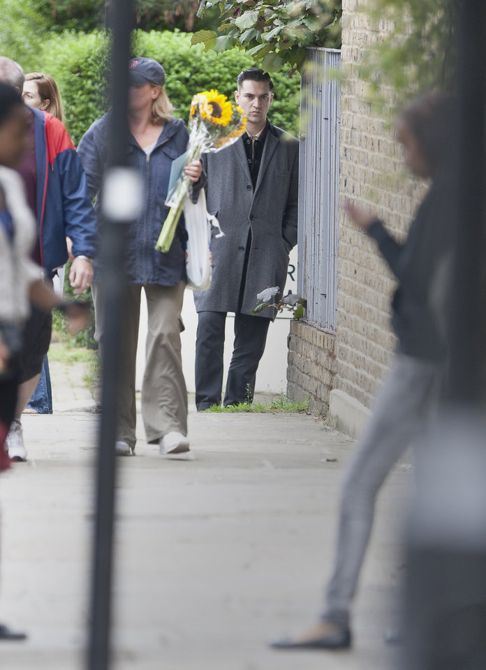 Photo - British singer and filmmaker Reg Traviss looks on as a member of the public passes to lay flowers near a police cordon by Camden Square, close to the home of British singer Amy Winehouse, who was found dead, Saturday, July 23, 2011.  Traviss and Winehouse are known to have a close relationship.  The cause of death was not immediately known, and London Ambulance Services said Winehouse had died before the two ambulance crews arrived at the scene. (AP Photo/Joel Ryan) ORG XMIT: LENT101