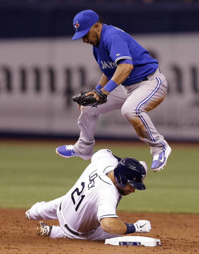 Photo - Toronto Blue Jays second baseman Maicer Izturis leaps over Tampa Bay Rays' James Loney after forcing Loney at second base on a fifth-inning fielder's choice by Rays' Desmond Jennings during a baseball game Monday, March 31, 2014, in St. Petersburg, Fla. (AP Photo/Chris O'Meara)