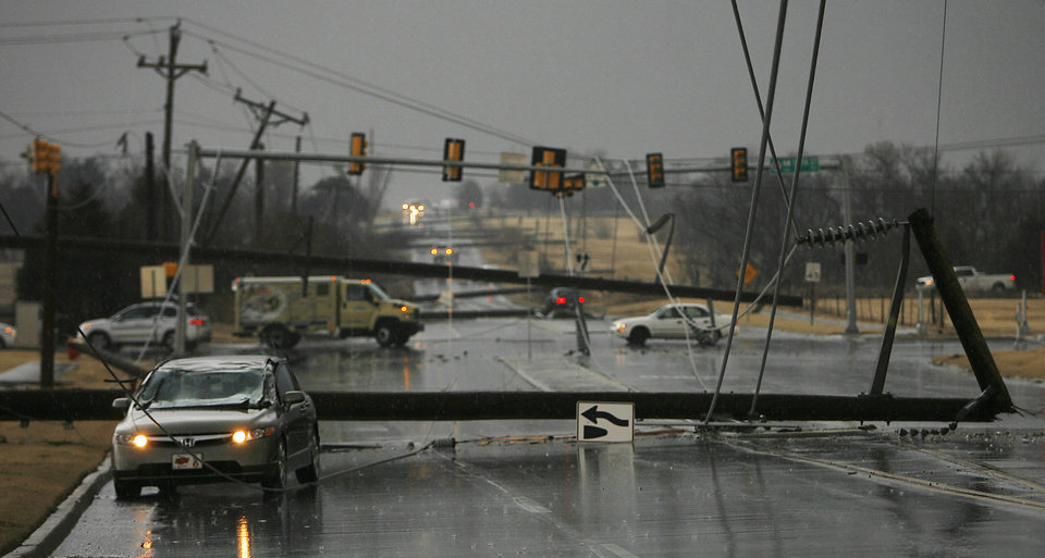 Photo - High line poles blown over as cars are on north Penn just south of 150 in Oklahoma City, Tuesday , February 10, 2009.  By David McDaniel, The Oklahoman.