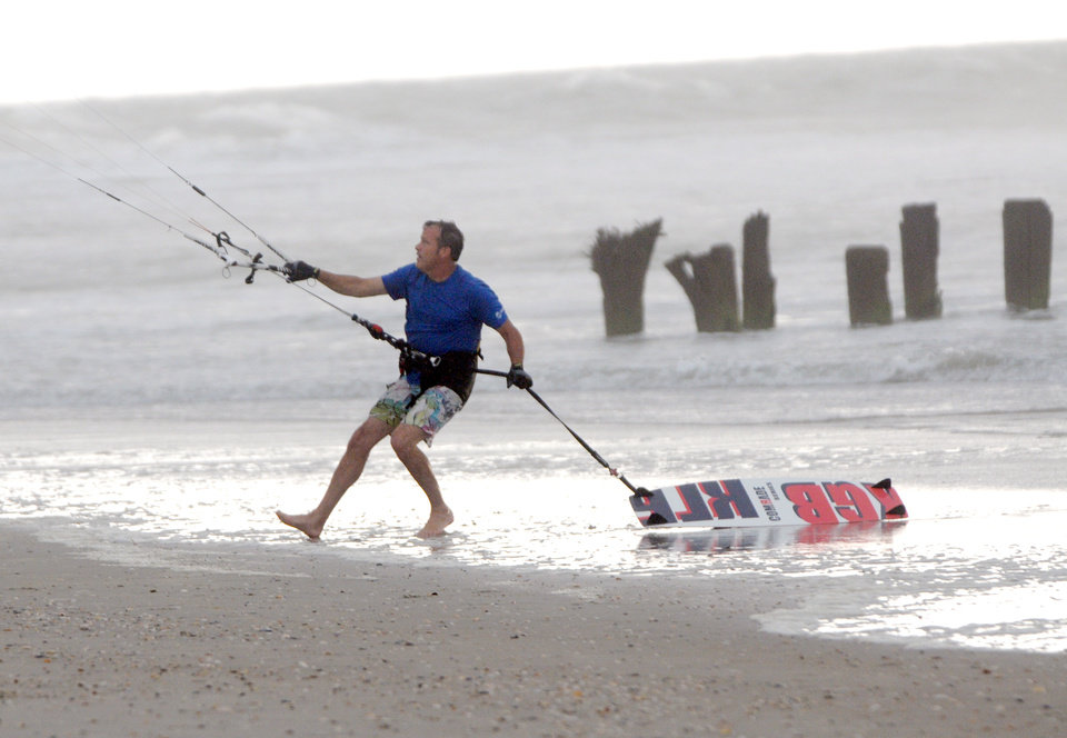 Photo - Kite boarder Pete Nero secures his kite as darks clouds and rain move in on the north end of Carolina Beach, N.C., Thursday, July 3, 2014. Residents along the coast of North Carolina are bracing for the arrival of the Hurricane Arthur, which threatens to give the state a glancing blow on Independence Day. (AP Photo/Wilmington Star-News, Mike Spencer)