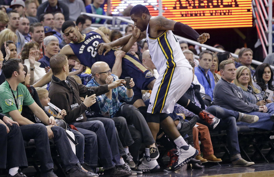 Photo - Utah Jazz's Derrick Favors, right, and New Orleans Pelicans' Anthony Davis (23) crash in to the fans in the second quarter during an NBA basketball game on Friday, April 4, 2014, in Salt Lake City. (AP Photo/Rick Bowmer)