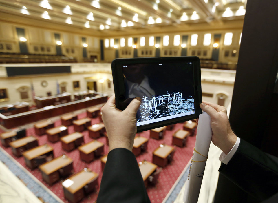 Photo -  Brian Sauer, director of mechanical engineering for FSB and part of a team of architects and engineers producing a 3D map of the state Capitol, uses an i-Pad to demonstrate the mechanical systems in the Senate Chambers of the building Friday in Oklahoma City. Photo by Paul Hellstern, The Oklahoman   PAUL HELLSTERN -  Oklahoman