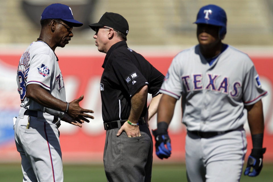 Texas Rangers manager Ron Washington, left, argues a force out call with second base umpire Lance Barksdale in the third inning of a baseball game against the Oakland Athletics, Wednesday, Oct. 3, 2012, in Oakland, Calif. At right is Nelson Cruz. (AP Photo/Ben Margot)