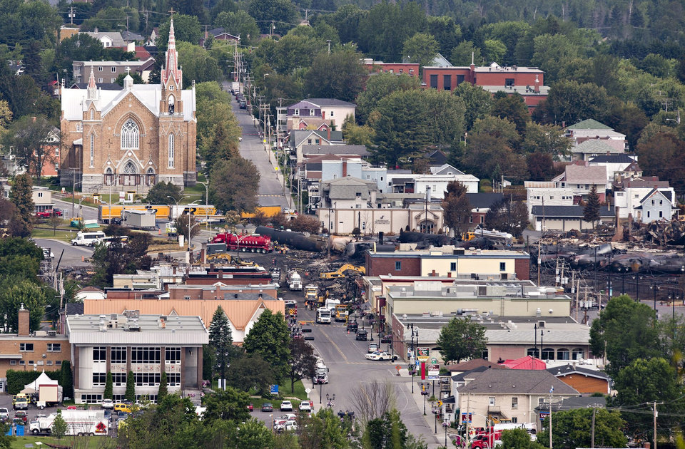 Photo - The Sainte-Agnès Catholic Church stands unscathed next to the derailment and blast site in Lac-Megantic, Que., Tuesday, July 9, 2013. Pope Francis  on Tuesday extended an apostolic blessing to victims, families and everyone affected by the tragedy.  (AP Photo/The Canadian Press, Jacques Boissinot)