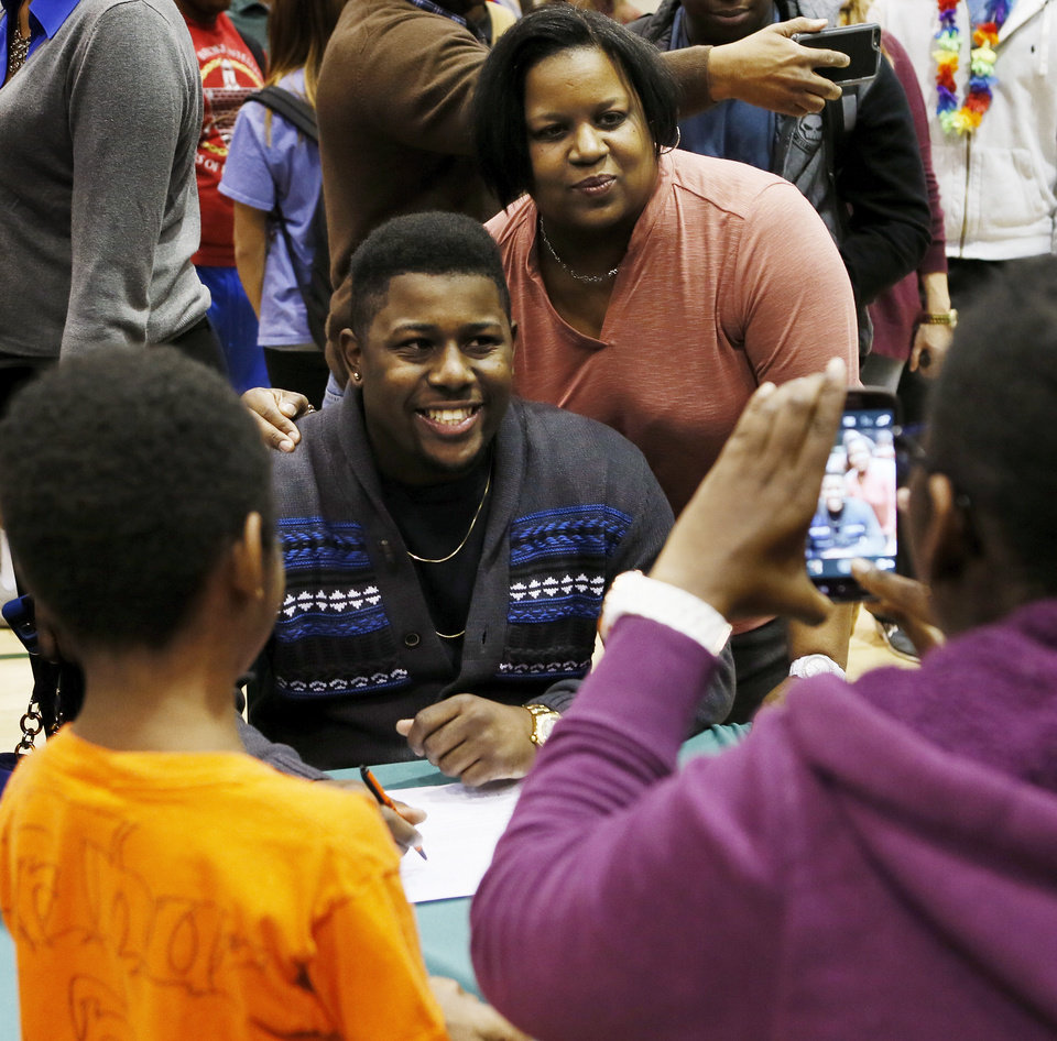 Photo - Ken Harris takes a picture with his mother, Marschelle Harris, during a national signing day ceremony at Edmond Santa Fe High School in Edmond, Okla., Wednesday, Feb. 4, 2015. Harris signed to play football at Langston. Photo by Nate Billings, The Oklahoman