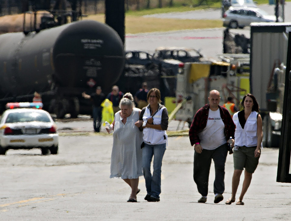 Photo - Volunteers escort evacuees to their home near the blast site to pick up some belongings Monday, July 8, 2013 in Lac-Megantic, Quebec.   A runaway train derailed Saturday igniting tanker cars carrying crude oil.   (AP Photo/THE CANADIAN PRESS, Ryan Remiorz