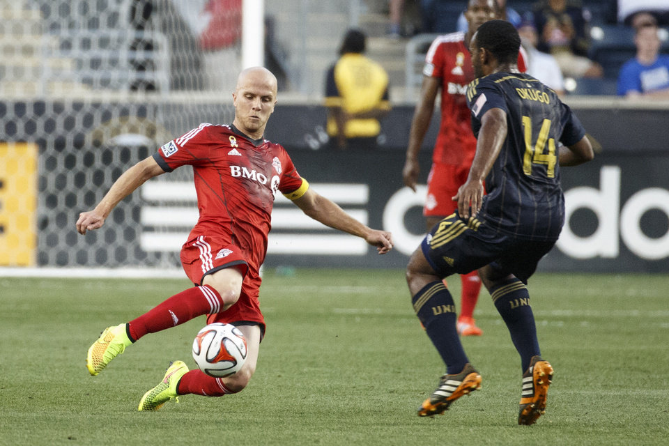 Photo - Toronto FC's Michael Bradley, left, goes for the ball as Philadelphia Union's Amobi Okugo, right, defends against him during the first half of an MLS soccer match, Wednesday, Sept. 3, 2014, in Chester, Pa. (AP Photo/Chris Szagola)