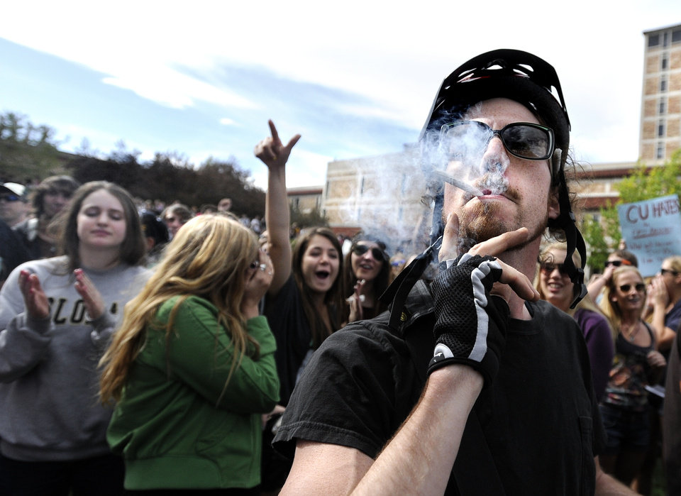 Photo -   An unidentified man smokes a marijuana cigarette outside of the Duane Physics building during the 4/20 rally on the University of Colorado campus in Boulder, Colo., on Friday, April 20, 2012. Many students at the University of Colorado and other campuses across the country have long observed 4/20. The counterculture observation is shared by marijuana users from San Francisco's Golden Gate Park to New York's Greenwich Village. (AP Photo/The Daily Camera, Jeremy Papasso)