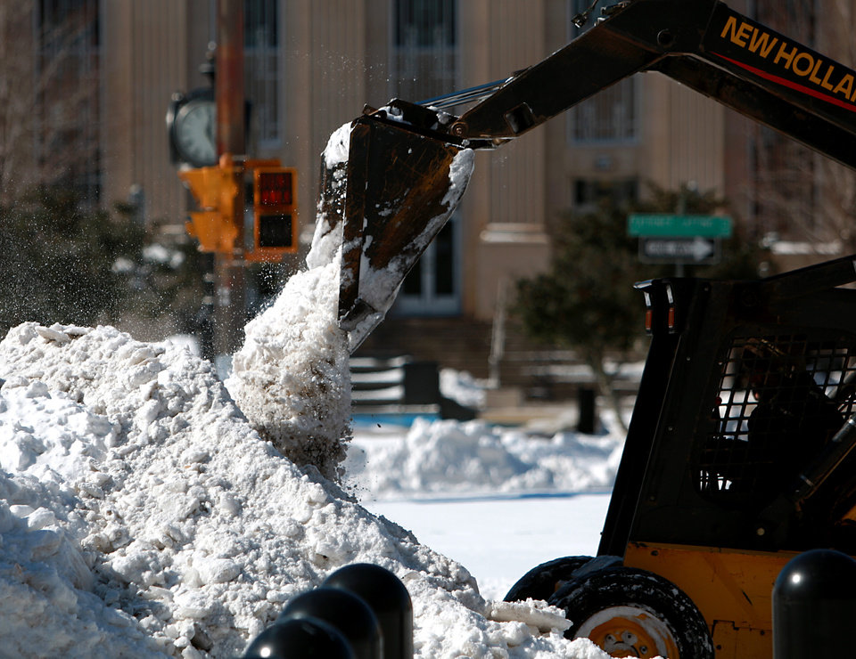 Photo - County employees use equipment to clean snow off of Hudson Ave. in front of the County Courthouse and the Oklahoma City Municipal Building in Oklahoma City on Wednesday, Feb. 2, 2011. Photo by John Clanton, The Oklahoman