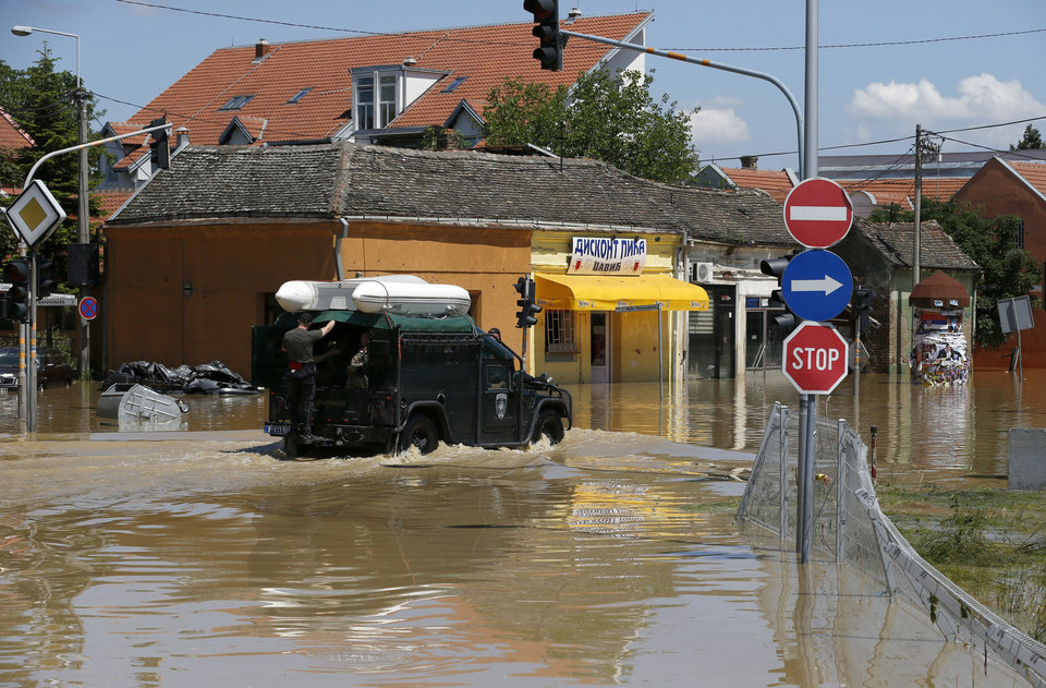 Photo - A police vehicle drives through flooded street in Obrenovac, some 30 kilometers (18 miles) southwest of Belgrade, Serbia, Monday, May 19, 2014. Belgrade braced for a river surge Monday that threatened to inundate Serbia's main power plant and cause major power cuts in the crisis-stricken country as the Balkans struggle with the consequences of the worst flooding in southeastern Europe in more than a century. At least 35 people have died in Serbia and Bosnia in the five days of flooding caused by unprecedented torrential rain, laying waste to entire towns and villages and sending tens of thousands of people out of their homes, authorities said. (AP Photo/Darko Vojinovic)