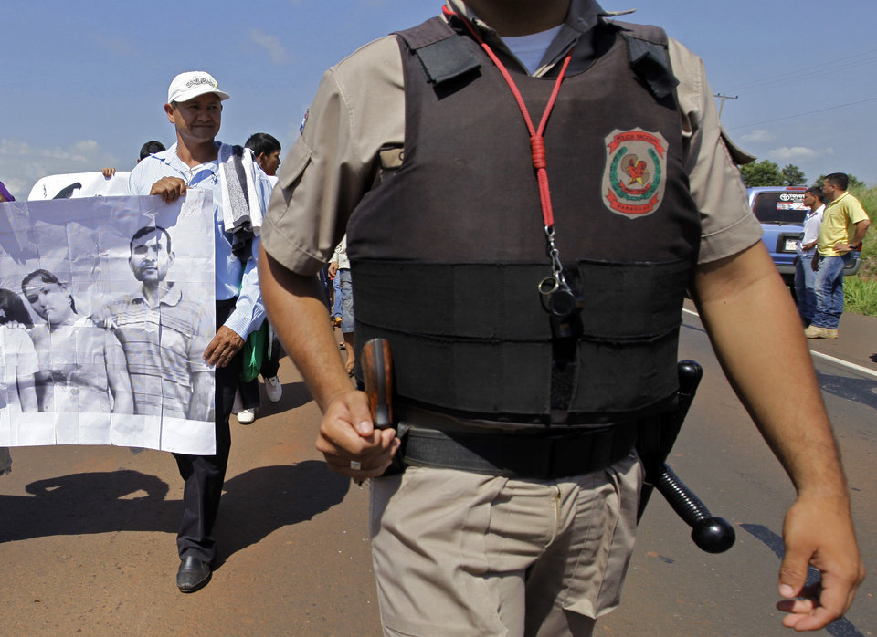 Photo - In this photo taken Nov. 15 2012 Vidal Vega, left,  holds a banner during a march to demand the freedom of landless farmers near Curuguaty city, Paraguay. Early Saturday gunmen murdered 48-year-old Vega, one of the surviving leaders of a peasant movement whose land dispute with a powerful politician prompted the end of Fernando Lugo's presidency last June.  He was hit four times by bullets from a 12-gauge shotgun and a .38-caliber revolver fired by two unidentified men at his house in the peasant settlement of  Yvy Pyta, in the outskirts of Curuguaty.(AP Photo/Jorge Saenz)