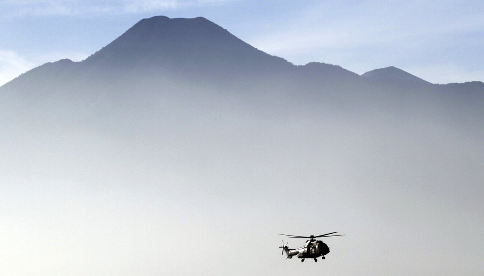 Photo -   An Indonesian helicopter carrying the bodies of victims of Wednesday's plane crash flies through Bogor, in West Java, Indonesia. Clearer weather finally allowed Indonesian helicopters to land Saturday and retrieve some remains of the 45 people aboard a Russian-made plane that crashed into the volcano during a demonstration flight. (AP Photo/Achmad Ibrahim)