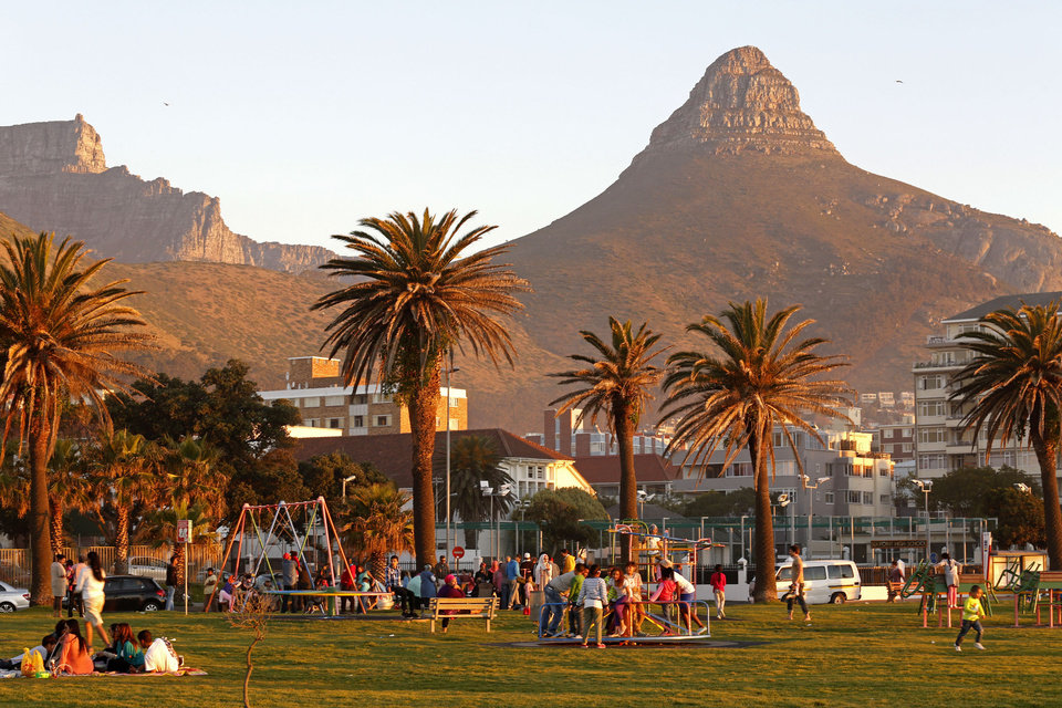Photo - In this photo taken on Sunday, Aug. 24, 2014, people enjoy sunset on a grass area at the promenade, with Table Mountain, left, and Lions Head, right, forming the backdrop, area's well known for their walking trails in Cape Town, South Africa.  Locals love this spot for sunset picnics, drinks and meeting friends. It offers views of Robben Island, Table Mountain and the seascape. There are easy trails from Signal Hill to the top of Lion's Head, and full moon hikes offer a chance to see spectacular glittering moonlight on the sea. (AP Photo/Schalk van Zuydam)