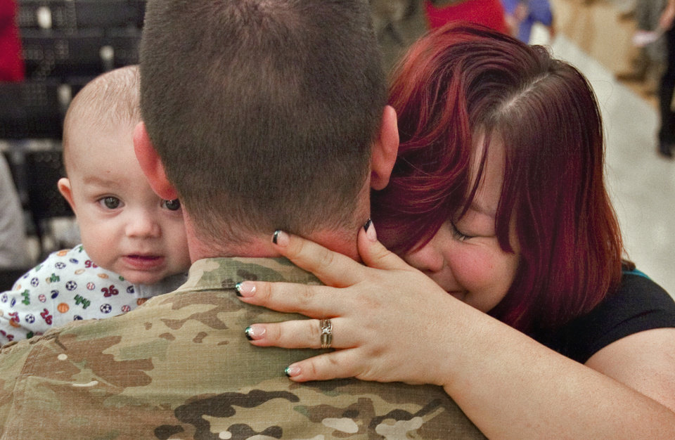 Spc. Galen Scott is greeted by his six-month-old son Benjamin and his wife Jennifer at a ceremony where he and other members of the Oklahoma National Guard were welcomed by family and friends upon their return from Afghanistan on Thursday, Jan. 12, 2012, in Norman, Okla. 