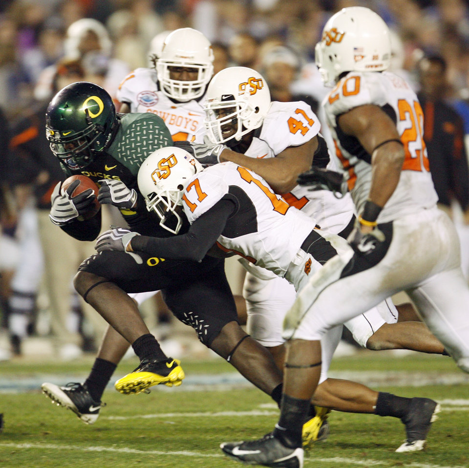 Photo - Oregon's LeGarrette Blount (9) gets past OSU's T.J. Bell (11), Jacob Lacey (17), Orie Lemon (41) and Andre Sexton (20) on a touchdown run in the fourth quarter of the Holiday Bowl college football game between Oklahoma State and Oregon at Qualcomm Stadium in San Diego, Tuesday, Dec. 30, 2008. Oregon won, 42-31. PHOTO BY NATE BILLINGS, THE OKLAHOMAN