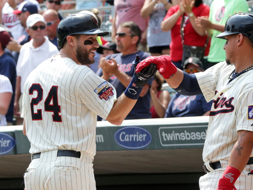 Photo - Minnesota Twins' Trevor Plouffe, left, is all smiles as he is greeted by Oswaldo Arica following Plouffe's two-run home run off San Diego Padres pitcher Odrisamer Despaigne in the first inning of a baseball game, Wednesday, Aug. 6, 2014, in Minneapolis. (AP Photo/Jim Mone)