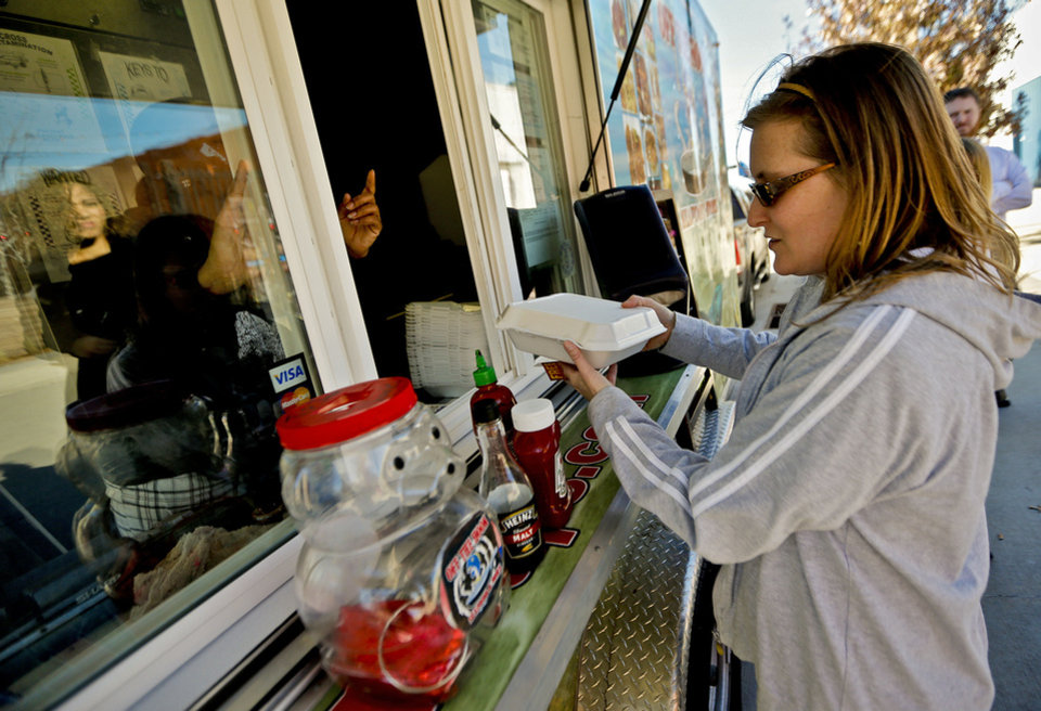 Photo - Becca Nolte buys her lunch from Off the Hook food truck at Dunlap Codding on Film Row in Oklahoma City, Okla., Wednesday, Dec. 18, 2013.  Dunlap Codding will turn Film Row into a winter market on Friday with crafts vendors, food trucks, drinks and live music. About 40 vendors plan to sell their wares at the event.Photo by Chris Landsberger, The Oklahoman