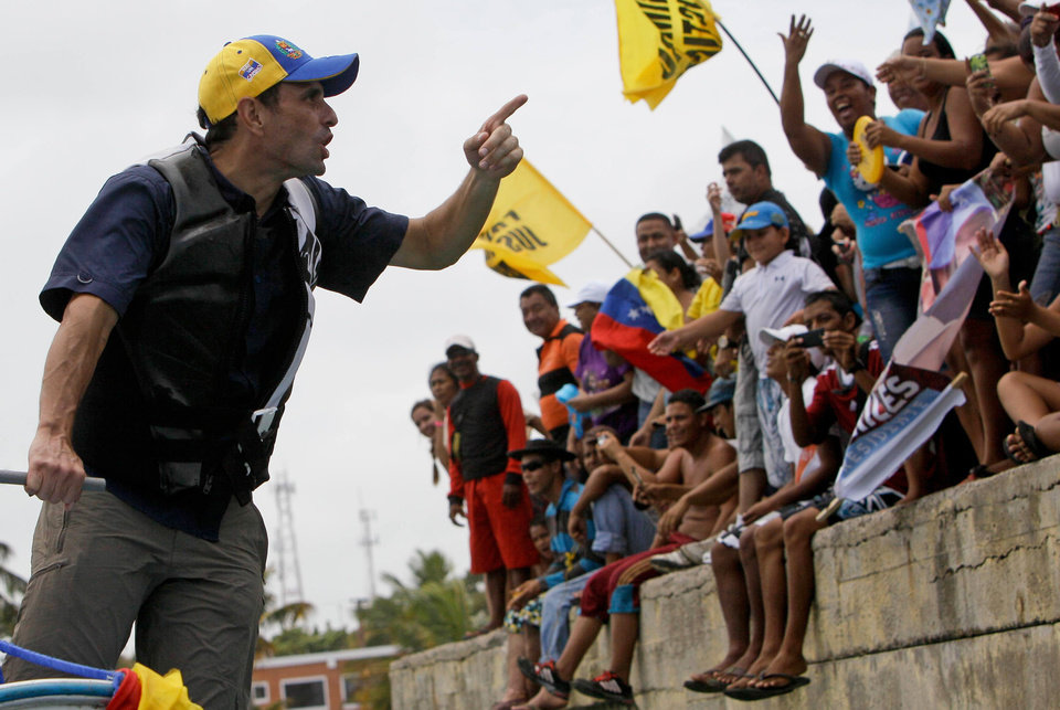 Opposition presidential candidate Henrique Capriles greets supporters during a campaign visit at Morrocoy Keys near Chichiriviche, Venezuela, on Good Friday, March 29, 2013. Holy Week in Venezuela is a time when millions traditionally take a welcome pause from work and politics to go on vacation. Yet that hasn\'t stopped Venezuela\'s time-pressed presidential candidates from sprinting through the holidays toward an April 14 election to replace the late Hugo Chavez, as they try to define both themselves and each other within weeks. Capriles will run against Chavez\'s chosen successor, acting President Nicolas Maduro.(AP Photo/Fernando Llano)