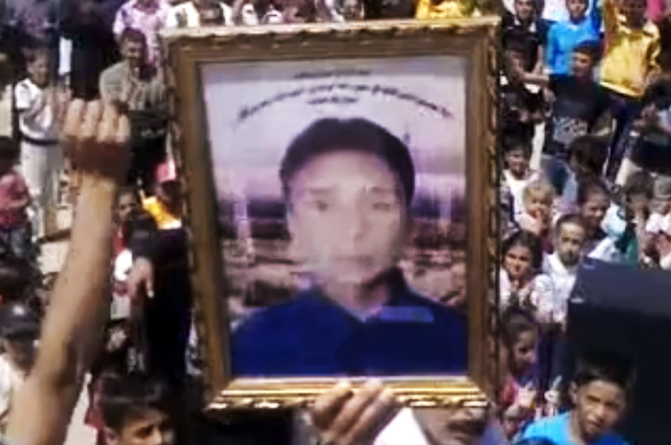 Photo -   This image made from amateur video released by the Shaam News Network and accessed Friday, May 4, 2012, purports to show a man holding the portrait of a boy during a demonstration in Hama, Syria. (AP Photo/Shaam News Network via AP video) TV OUT, THE ASSOCIATED PRESS CANNOT INDEPENDENTLY VERIFY THE CONTENT, DATE, LOCATION OR AUTHENTICITY OF THIS MATERIAL