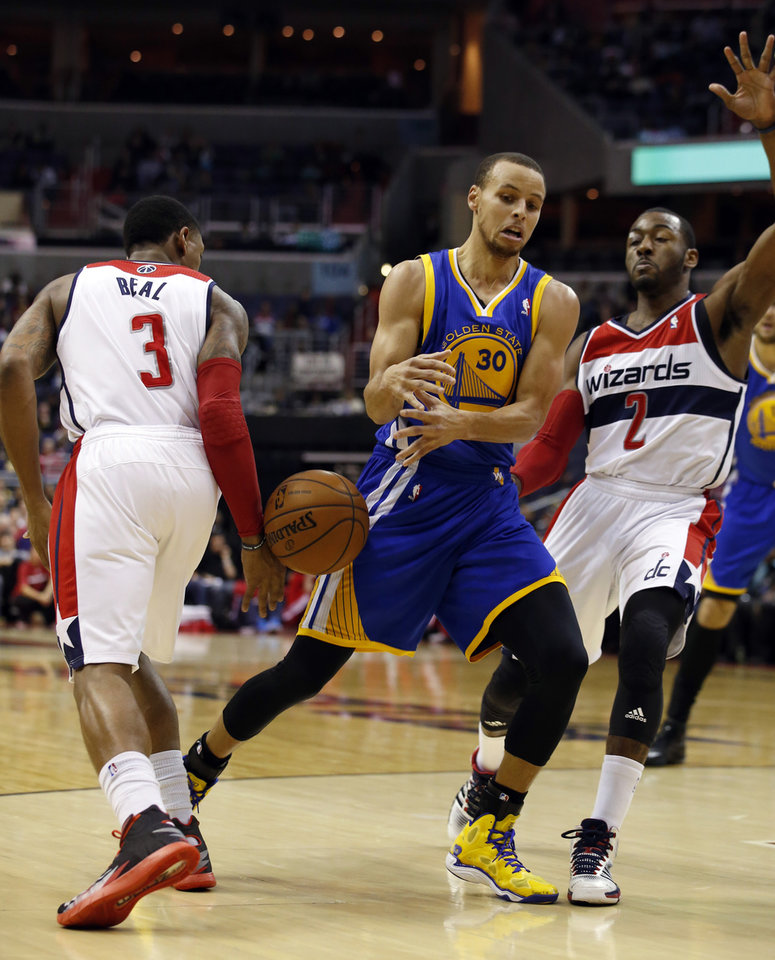 Photo - Golden State Warriors guard Stephen Curry (30) has the ball knocked away by Washington Wizards guard Bradley Beal (3) with guard John Wall (2) nearby in the first half of an NBA basketball game on Sunday, Jan. 5, 2014, in Washington. (AP Photo/Alex Brandon)